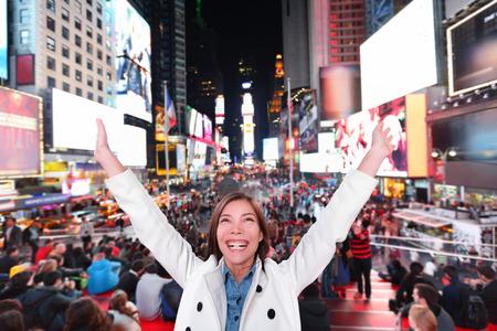 幸せな興奮して女ニューヨーク市、マンハッタン タイムズ スクエアで腕を上げるとうれしそうな夜を祝うを応援します。陽気な民族アジア白人笑み 写真素材