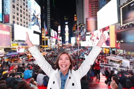Happy excited woman in New York City, Manhattan, Times Square cheering celebrating joyful at night with arms raised. Smiling cheerful Multiethnic Asian Caucasian young urban professional in her 20s.