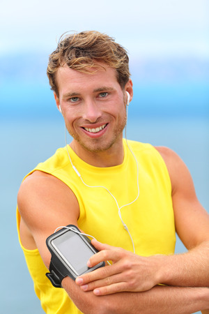Running app on smartphone. Male runner listening to music adjusting settings on armband for smart phone. Fit man fitness model working outdoor by water. photo
