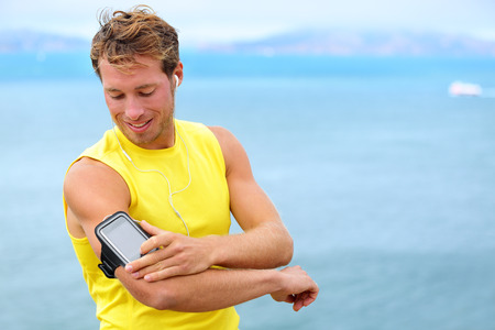 armband: Running training music on smartphone app. Runner man listening to music adjusting settings on armband for smart phone. Fit male fitness model working outdoor by water. Stock Photo