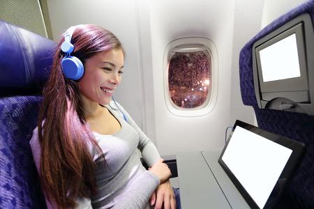 flug: Flugzeug Passagier im Flugzeug, bei dem Tablet-Computer. Frau im Flugzeug-Kabine mit intelligenten Gerät Musik hören über Kopfhörer. Lizenzfreie Bilder