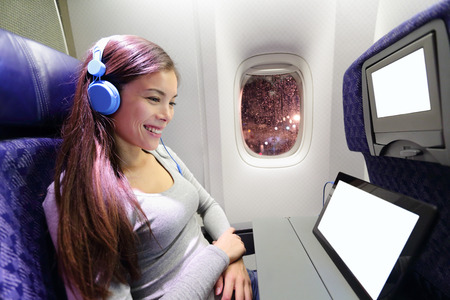 Plane passenger in airplane using tablet computer. Woman in plane cabin using smart device listening to music on headphones. Stock Photo