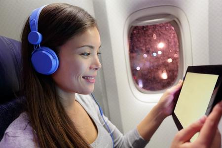 タブレット コンピューターを使用して航空機の乗客。ヘッドフォンで音楽を聞くスマート デバイスを使用して飛行機の機内で女性。