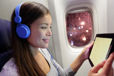 passenger aircraft: Passenger in airplane using tablet computer. Woman in plane cabin using smart device listening to music on headphones.