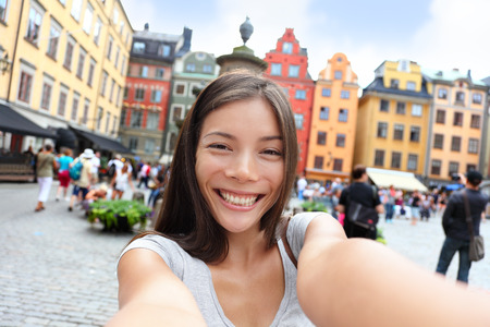 Asian woman taking self portrait selfie photo on Europe travel. Happy candid tourist on Stortorget, big square, Gamla Stan, the old town of Stockholm, Sweden.