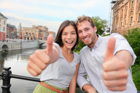 Thumbs up couple happy in Stockholm, Sweden. Excited people giving thumbs up gesture looking at camera. Multiracial young couple walking outside in Stockholm. Scandinavian man, Asian woman. photo
