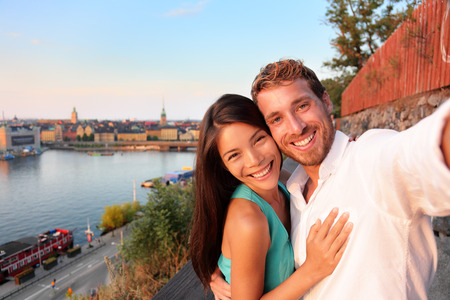 Couple taking selfie self portrait in Stockholm. Candid fresh Scandinavian man and Asian woman looking at old town cityscape sunset view from Monteliusvagen overlooking Gamla Stan, the old city.