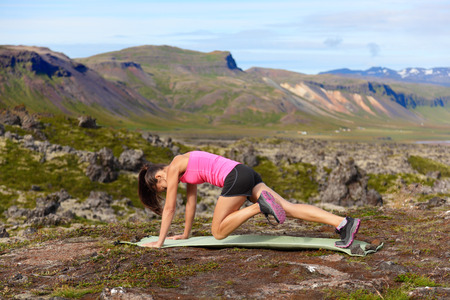 exercises: Exercising fitness woman doing exercises in nature. Girl doing mountain climbers exercise training outside in amazing landscape on Iceland. Fit female Asian Caucasian athlete sport model . Stock Photo