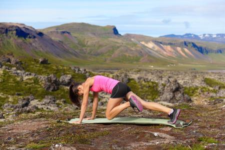 motion: Träning fitness kvinna gör övningar i naturen. Tjej gör bergsklättrare Fysisk träning ute i fantastiska landskap på Island. Passform kvinnliga Asiat Kaukasisk idrottsman idrottsmodellen. Stockfoto