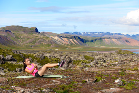 situp: Fitness woman doing russian twist core exercise outside. Fit female training stomach in amazing nature landscape on Iceland. Fit female sport model girl training crossfit outdoors. Mixed race athlete.