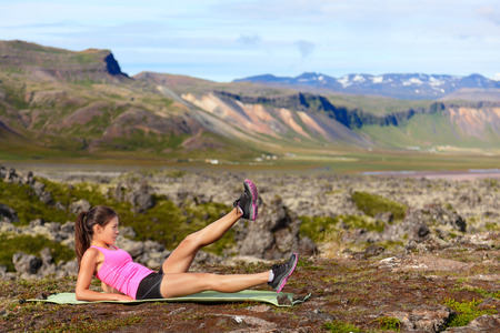 Fitness woman exercising in nature working on core strength doing scissor kick and flutter kicks exercise outdoor in amazing landscape on Iceland.