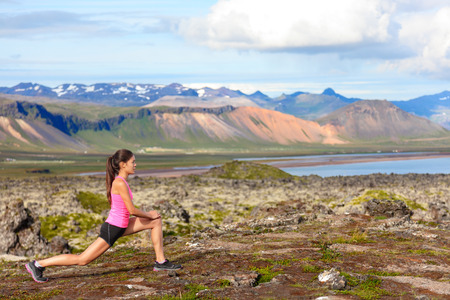 lunges: Fitness girl doing lunges exercise in nature. Female sport model exercising doing front forward lunge training legs and glute outside in beautiful landscape on Iceland. Stock Photo