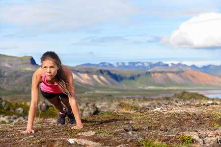 pushups: Push-ups fitness woman doing pushups or plank outside in amazing nature landscape on Iceland. Fit female sport model girl training crossfit outdoors. Mixed race Asian Caucasian athlete in her 20s. Stock Photo
