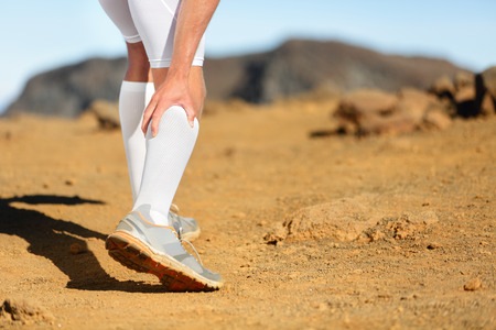 Running Cramps in leg calves or sprain calf on runner. Sports injury concept with running fitness man athlete outside. Stock Photo