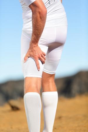 muslos: Ejecución de una lesión deportiva. Tirón muscular isquiotibial, distensión muscular o calambre muscular en la pierna de atrás del muslo del hombre correr al aire libre. Foto de archivo