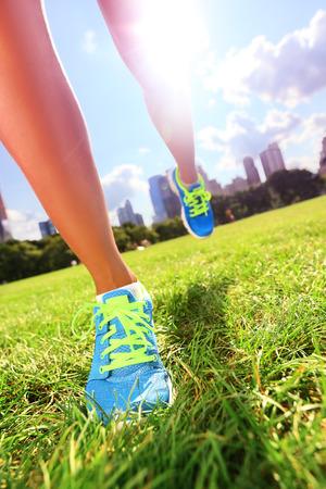 Runner - loopschoenen close-up van vrouw atleet loopschoenen op gras. De schoenen van vrouwelijke joggervrouwen in Central Park, de Stad van New York. Stockfoto
