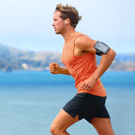man exercise: Running app on smartphone. Male runner listening to music jogging with armband for smart phone. Fit man fitness model working outdoor by water. Stock Photo