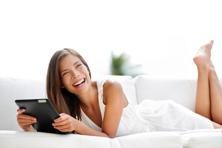lying on couch: Tablet computer. Young woman laughing in sofa lying down. Lifestyle with young caucasian asian mixed race woman model smiling using tablet pc in sofa at home outdoor in summer smiling happy.