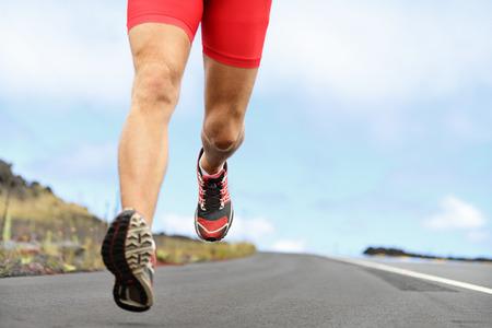 Running sport schoenen en benen. Man runner benen en schoenen in actie op de weg buiten bij zonsondergang. Mannelijke atleet model.