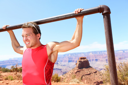 strong chin: Exercising Fitness athlete man training pull ups in amazing nature landscape of Grand Canyon. Strength training fit male working out exercising outdoors in summer doing pull-ups and chin-ups.