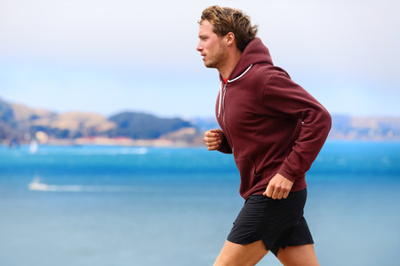 Runner athlete man running in sweatshirt hoodie in autumn fall by the water. Male runner training outdoors jogging in nature. photo