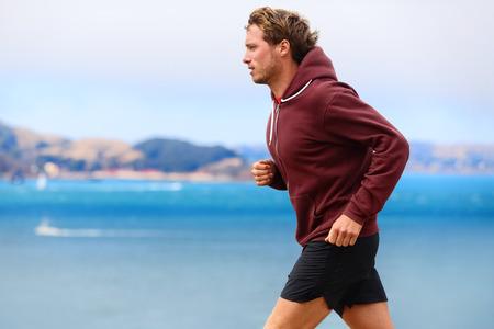 Runner atleet man loopt in sweatshirt hoodie in de herfst vallen door het water. Mannelijke agent opleiding buiten joggen in de natuur.