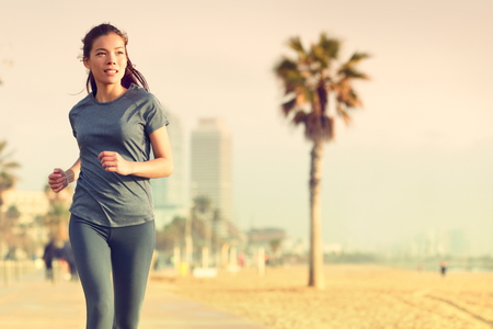 asian trees: Running woman jogging on beach boardwalk. Healthy lifestyle girl runner training outside working out. Mixed race Asian Caucasian fitness woman exercising outdoors. Stock Photo