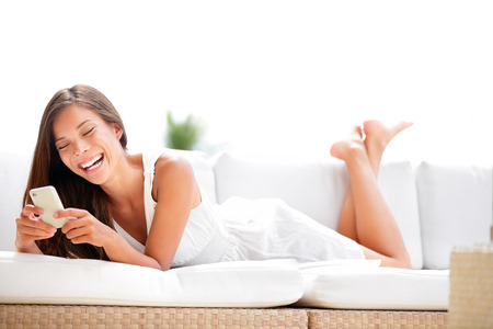 lying on couch: Smartphone woman using app on mobile smart phone lying in soda smiling happy. Beautiful multiracial girl sms text messaging or using application while lying on sofa. Asian Caucasian model in her 20s.