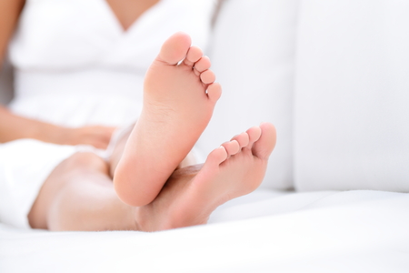bare body women: Woman feet closeup - barefoot woman relaxing in sofa. Close up of female feet of young beautiful woman sitting in couch outside.