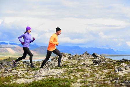 Running people trail runners in cross country run. Woman and man runners training jogging outdoors in beautiful mountain nature landscape on Snaefellsnes, Iceland. photo