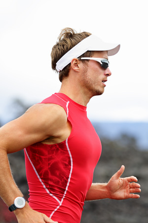 triathlon: Running triathlon athlete man. Runner triathlete training for ironman wearing sports sunglasses. Young Male athlete running in red compression top.