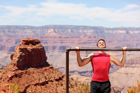 pullups: Fitness athlete man training pull ups in amazing nature landscape of Grand Canyon. Strength training fit male working out exercising outdoors in summer doing pull-ups and chin-ups.