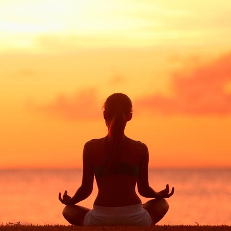 瞑想 - ヨガの女性の穏やかなビーチの夕日で瞑想します。ヨガの休日リゾート後退中に海の水で穏やかな禅瞬間にロータス ポーズでリラックス女の 写真素材