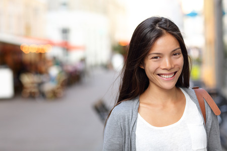 Asian woman candid portrait from street in Copenhagen city, Denmark. Young urban female smiling looking at camera. photo