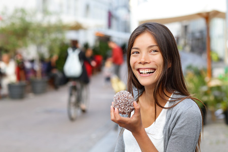 Woman eating traditional danish food floedeboller also called cream buns or marshmallow teacake. Girl enjoying the chocolate covered treat outside in city street of Copenhagen, Denmark. photo