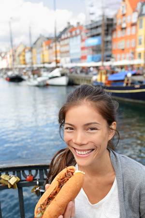 Woman eating traditional danish fast food snack hot dog. Girl enjoying hot dogs outside in Nyhavn waterfront canal street of Copenhagen, Denmark. photo