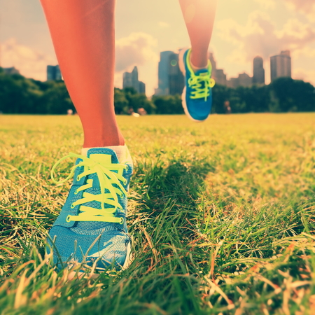 young womens: Healthy lifestyle runner - running shoes on woman athlete running shoes on grass. Female jogger womens shoes in Central Park, New York City. Stock Photo