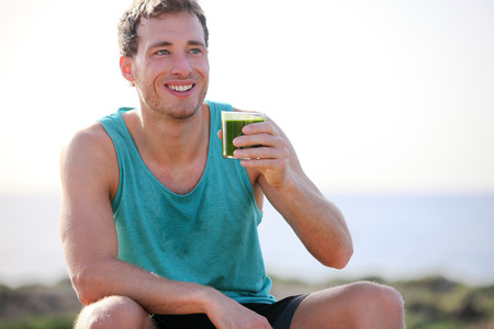 fruit smoothie: Green smoothie man drinking vegetable juice after running sport fitness training. Healthy eating lifestyle concept with young man outdoors.
