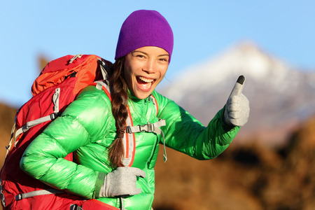 Hiking woman in winter jacket giving thumbs up smiling. Young Asian woman hiker smiling joyful at camera outdoor on hike trip. Beautiful young mixed race Asian Chinese  Caucasian woman in mountain. photo
