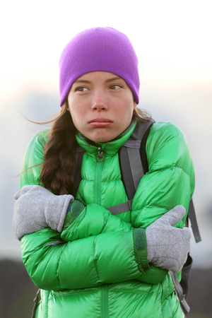 Freezing woman feeling cold outdoors trying to keep warm shaking and shivering wearing hat and gloves outside hiking on hike. Stockfoto