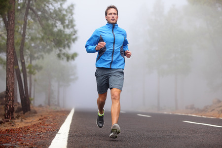 Healthy running runner man workout on mountain road. Jogging male fitness model working out training for marathon on forest road in amazing nature landscape.