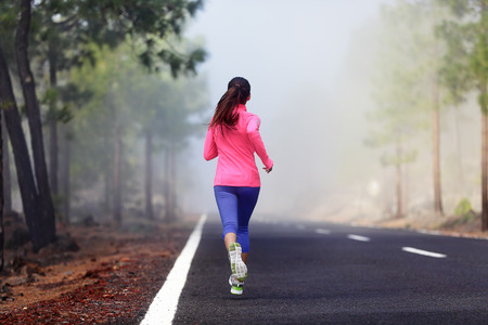 Healthy running runner woman workout on mountain road. Jogging female fitness girl working out training for marathon on forest road in amazing nature. Banque d'images