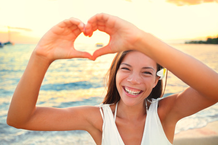 gesture: Love vacation - woman showing heart on beach. Girl gesturing heart shaped hands smiling happy and loving at camera. Pretty joyful multicultural Asian Caucasian girl.