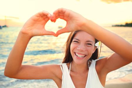 gestos: Vacaciones de amor - la mujer que muestra el coraz�n en la playa. Muchacha que gesticula las manos en forma de coraz�n sonriente feliz y amorosa a la c�mara. Bastante muchacha alegre cauc�sico asi�tico multicultural.