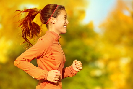 Woman runner running in fall autumn forest. Female fitness girl jogging on path in amazing fall foliage landscape nature outside.