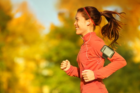 Woman runner running in fall autumn forest listening to music on smartphone using earphones. Female fitness girl jogging on path in amazing fall foliage landscape nature outside. Banque d'images