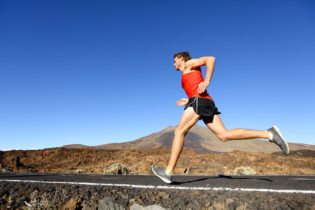 Deporte que se ejecuta el hombre - la formación corredor masculino al aire libre corriendo en carretera de montaña en el increíble paisaje de la naturaleza. Montar guapo corredor trabajando para el maratón fuera en verano.