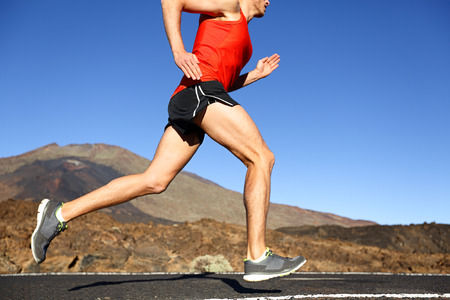 road runner: Running man - male runner training outdoors sprinting on mountain road in amazing landscape nature. Close up of fit handsome jogger working out for marathon outside in summer. Stock Photo