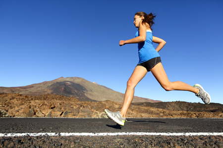 Sprinting running woman - female runner training outdoors jogging on mountain road in amazing landscape nature. Fit beautiful fitness model working out for marathon outside in summer. photo