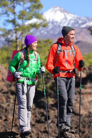 Hikers people hiking - healthy active lifestyle. Hiker couple hiking in beautiful mountain nature landscape. Woman and man hikers walking during hike on volcano Teide, Tenerife, Canary Islands, Spain. photo